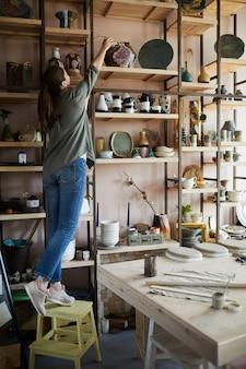Vrouw die keramiek op plank opslaat