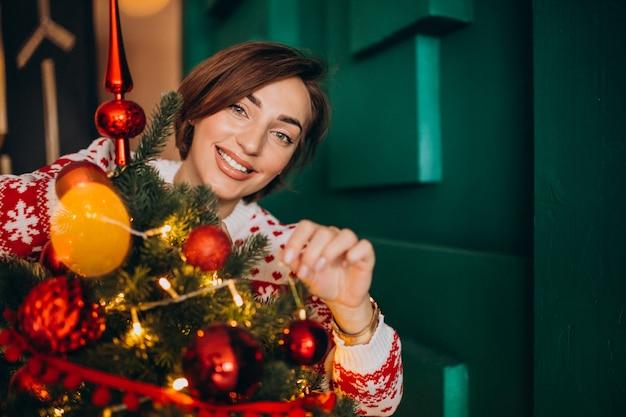 Vrouw die kerstboom met rode ballen verfraait