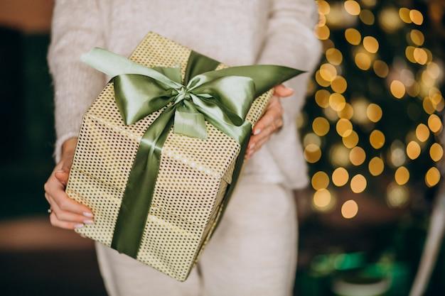 Vrouw die kerstmis huidig, doos dicht tegenhouden