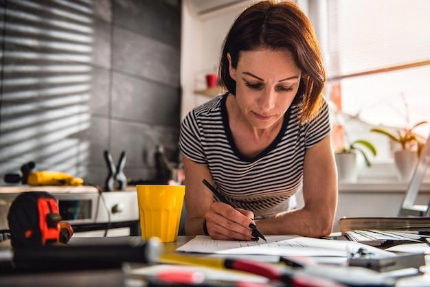 Vrouw die keukenblauwdrukken controleert