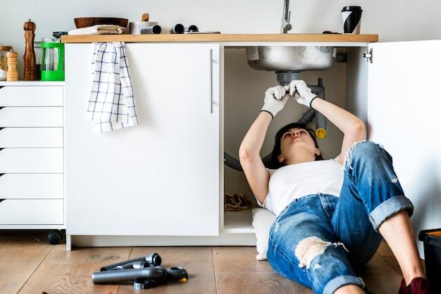 Vrouw die keukengootsteen bevestigt