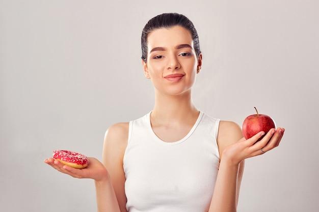 Vrouw die keuze maakt tussen appel en donut op witte achtergrond