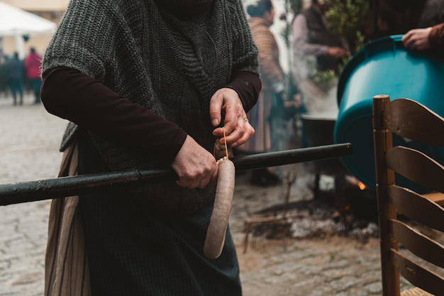 Vrouw die kielbasa aan een pijp hangt, omringd door mensen