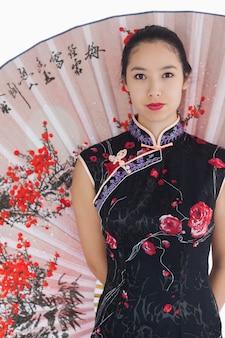 Vrouw die kimono draagt die zich met grote ventilator bevindt