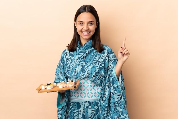 Vrouw die kimono draagt en sushi houdt over geïsoleerde achtergrond die een geweldig idee benadrukt