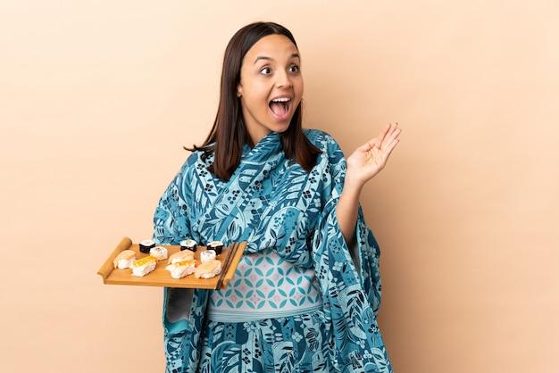 Vrouw die kimono draagt en sushi houdt