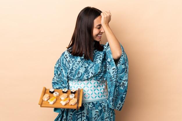 Vrouw die kimono draagt en sushi over de muur houdt, heeft iets gerealiseerd en heeft de oplossing voor ogen