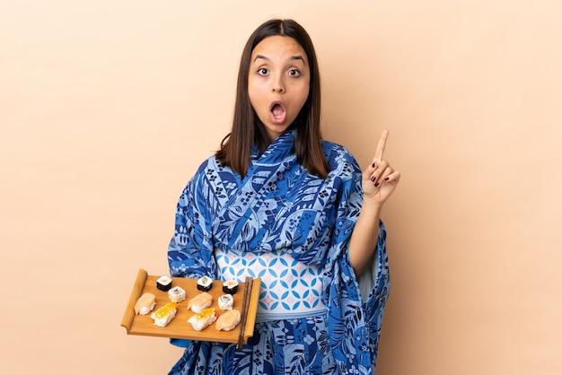 Vrouw die kimono draagt en sushi over geïsoleerde achtergrond houdt die van plan is om de oplossing te realiseren terwijl het opheffen van een vinger