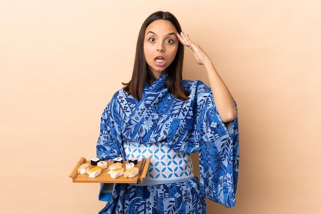 Vrouw die kimono draagt en sushi over muur met verrassingsuitdrukking houdt