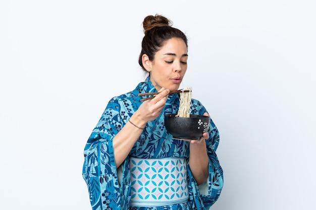 Vrouw die kimono over geïsoleerde witte muur draagt die een kom van noedels met eetstokjezand houdt die het blaast omdat zij heet zijn
