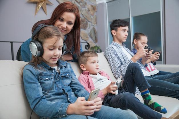 Vrouw die kinderen bekijkt die videospelletjes spelen