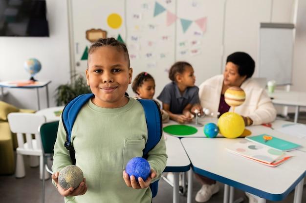 Vrouw die kinderen over planeten onderwijst
