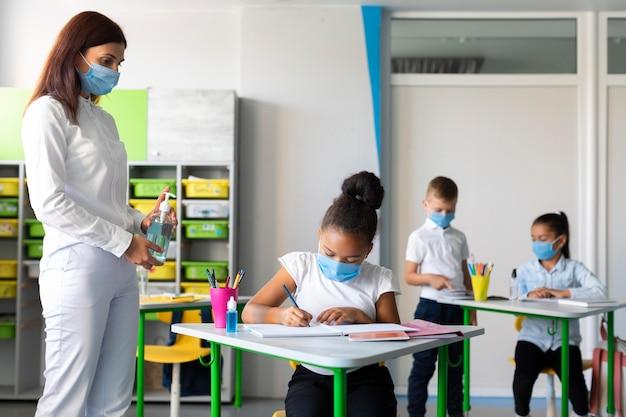 Vrouw die kinderen pandemische preventie in de klas onderwijst