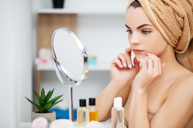 Vrouw die klaar voor het werk wordt dat ochtendmake-up in badkamerspiegel thuis doet