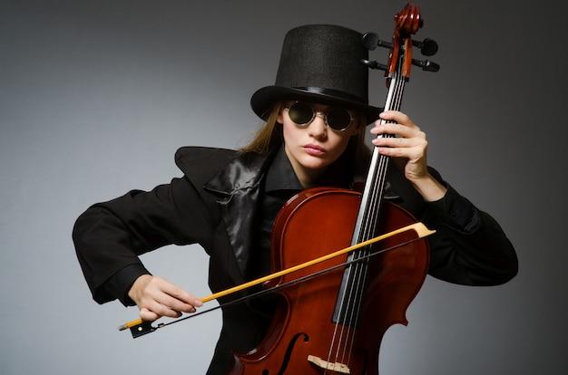 Vrouw die klassieke cello in muziek speelt