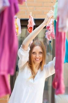 Vrouw die kleding hangt om na de was te drogen