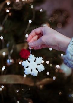 Vrouw die kleine sneeuwvlok in hand houdt