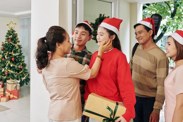 Vrouw die kleinkinderen vrolijke kerstmis wenst