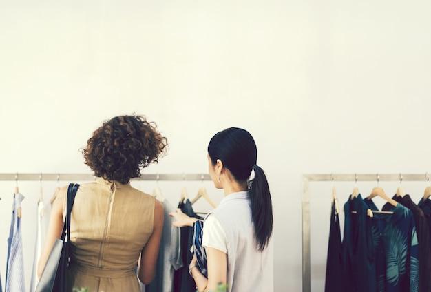 Vrouw die kleren in een winkel controleren