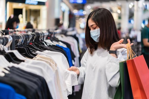 Vrouw die kleren kiest bij winkelcomplex en medisch masker draagt voor preventie van coronavirus