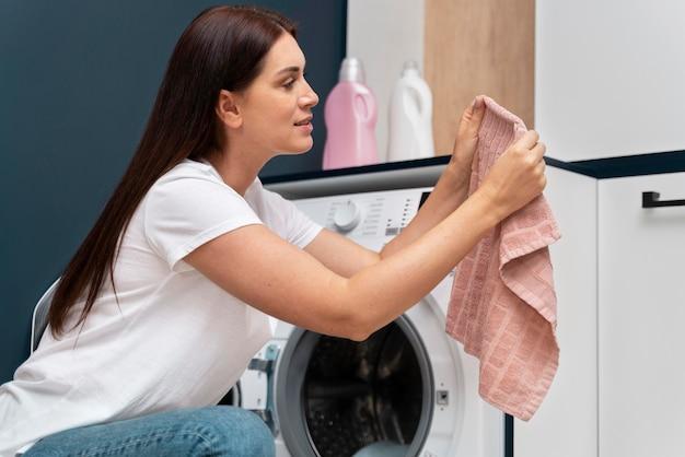 Vrouw die kleren uit de wasmachine haalt