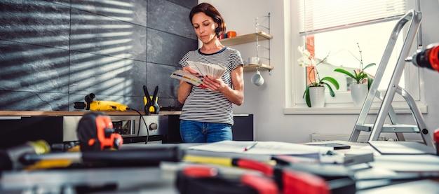 Vrouw die kleurenmonster controleert bij nieuwe keuken