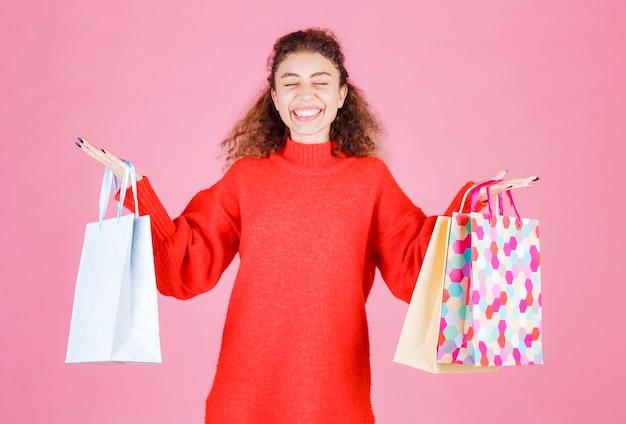 Vrouw die kleurrijke boodschappentassen vasthoudt en zich gelukkig voelt.