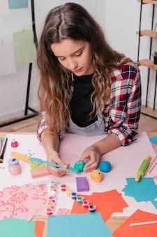 Vrouw die kleurrijke klei voor het maken van beeldverhaalgezicht snijdt