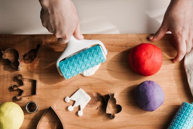 Vrouw die kleurrijke plasticine op houten raad vormen