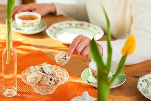 Vrouw die koekjes van koffietafel neemt