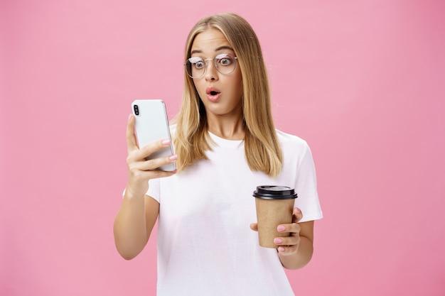 Vrouw die koffie drinkt, geschokt door ontvangen bericht, reagerend op verbluffend nieuws, lippen vouwend naar adem...