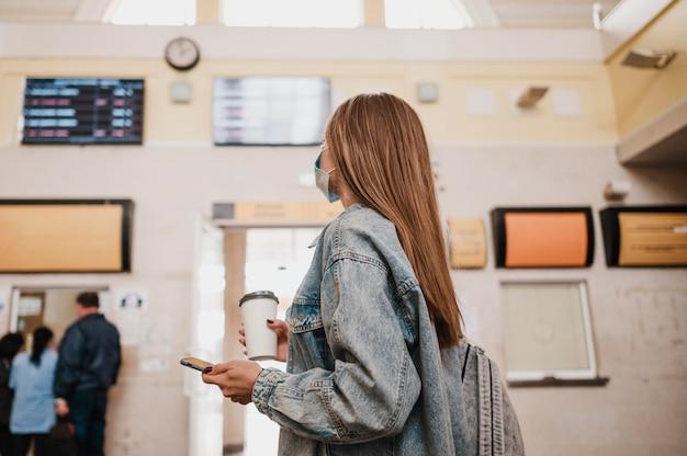 Vrouw die koffie houdt en in een treinstation is