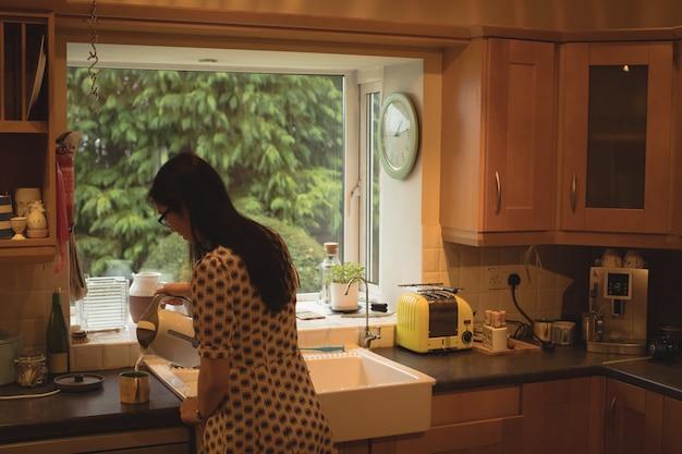 Vrouw die koffie in keuken voorbereidt