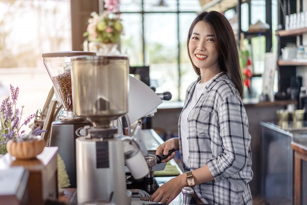 Vrouw die koffie met machine in koffie voorbereidt