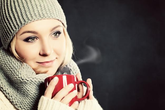 Vrouw die koffie of thee drinkt. winterdrankje