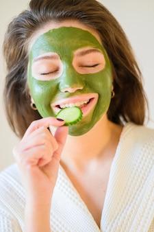 Vrouw die komkommerplak eet terwijl het hebben van een gezichtsmasker