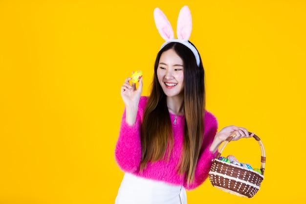 Vrouw die konijntjesoren draagt die een mand houden
