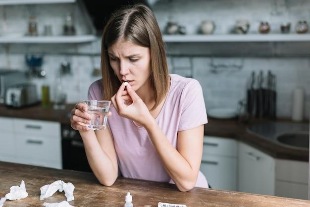 Vrouw die koorts heeft die geneeskunde thuis neemt