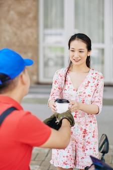 Vrouw die kopje koffie ontvangt