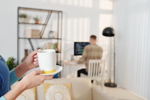 Vrouw die kopje lekkere koffie brengt aan echtgenoot die op de achtergrond aan programmeercode werkt