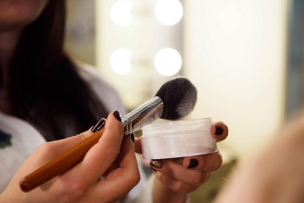 Vrouw die kosmetisch poeder met leeswijzer, het concept van de huidzorg toepast.