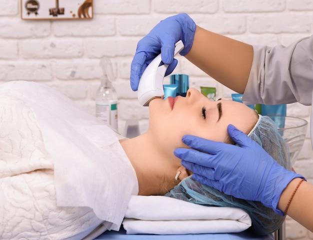 Vrouw die kosmetische procedures in kuuroordkliniek doet.