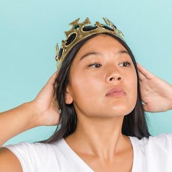 Vrouw die kroon draagt en weg kijkt