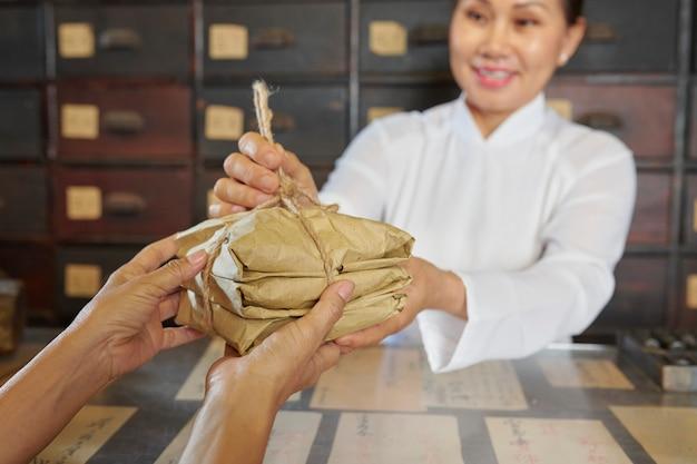 Vrouw die kruiden in apotheker verkoopt
