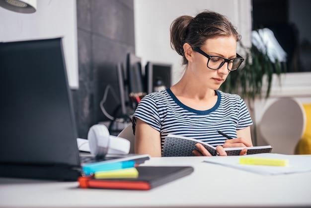 Vrouw die laat op het kantoor werkt