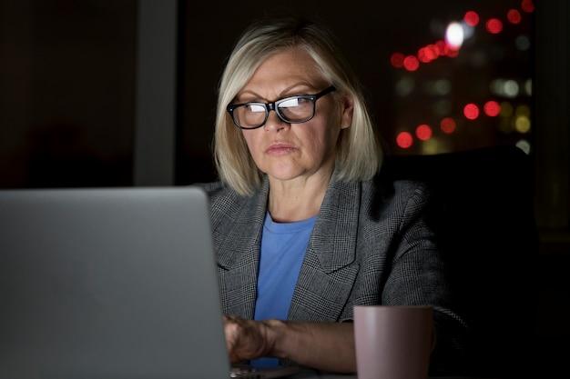 Vrouw die laat op kantoor werkt