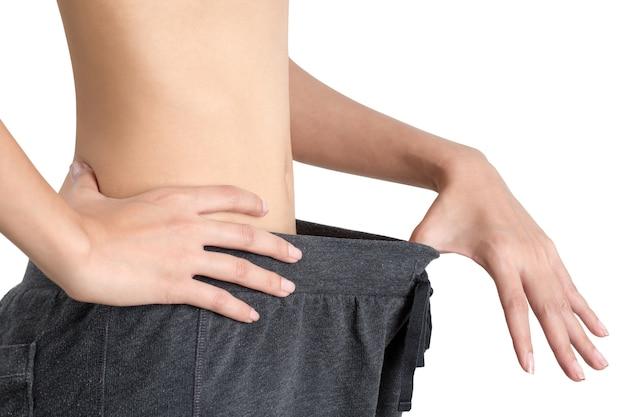 Vrouw die laat zien hoeveel gewicht ze heeft verloren - afvallen en een gezond lichaamsconcept