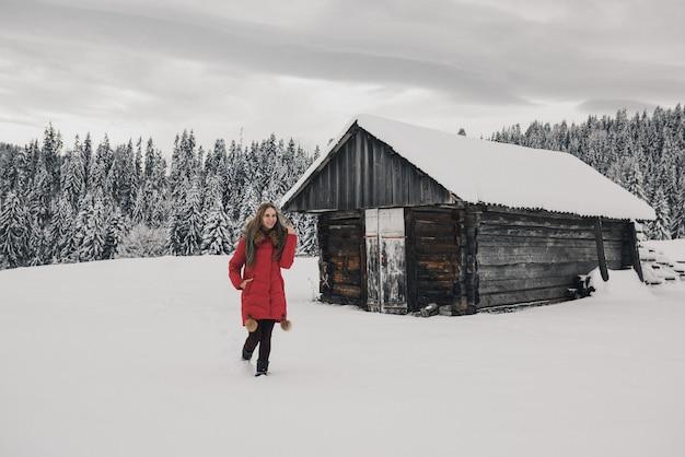 Vrouw die lacht in de buurt van houten huisje in de winter