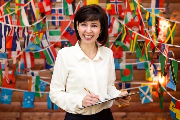 Vrouw die lacht met succes internationaal onderhandelen. muur van vlaggen van de wereld