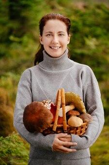 Vrouw die lacht naar de camera houdt een rieten mand met champignons in haar handen concept van biologisch voedsel organic